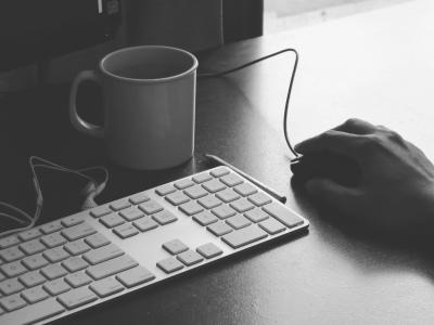 Keyboard and mouse accompanied by coffee mug